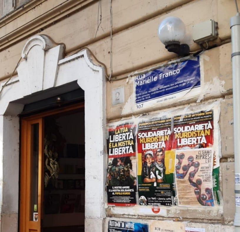 Numa rua do Trastevere, uma placa azul com a inscrição 'Rua Marielle Franco'.